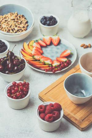 Granola paleo vegana cruda o muesli hecho de nueces. Plato de bayas de frutas, fresas, arándanos, frambuesas, melocotón, higos, grosella roja, vista lateral, tonos, enfoque selectivo Foto de archivo