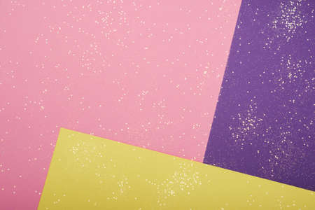 Golden glitter scattered on the pink purple yellow card background, top view, selective focus