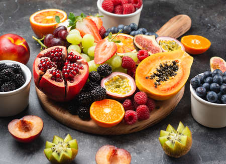 Delicious fruit platter pomegranate papaya oranges passion fruits berries on wooden board on dark concrete background, selective focus, copy space