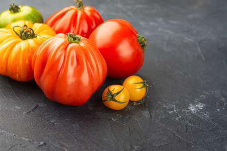 Selection of organic large heirloom and cherry tomatoes close up on dark blue concrete background, selective focus Stock Photo