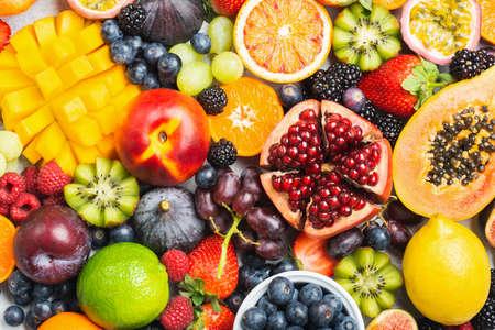 Heerlijke gezonde fruitachtergrond mango papaya aardbeien sinaasappelen passievruchten bessen, bovenaanzicht, selectieve focus Stockfoto