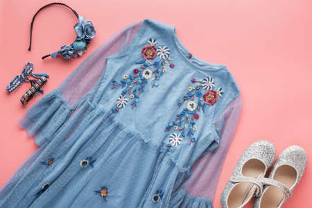 Girls' fashion background, blue tulle dress with embroidery, sparkly shoes, flower headband, bracelets and necklace on pink, flat lay, top view, selective focus Standard-Bild