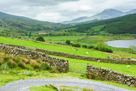 Track to Snowdon summit taking ranger path, North Wales, United Kingdom, view of the mountains, lake, stone wall, selective focus Banco de Imagens