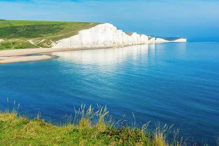 Hope Gap beach near Seaford, East Sussex, England. South Downs National park. View of blue sea, cliffs, beach, green fields, selective focus