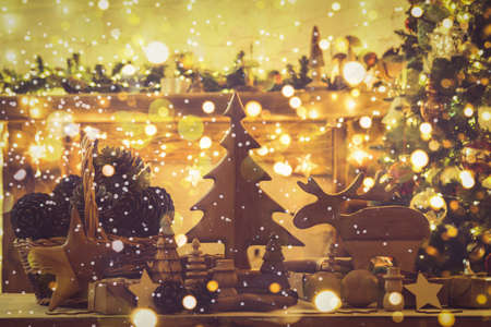 Christmas composition, wooden toys, figures, stars, moose, fur tree on table in front of fireplace, decorated mantel, fir tree with baubles, ornaments, lights with beautiful bokeh, selective focus