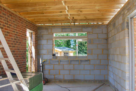 Renovation projects. Building of extension of the existing house, finished brick and block walls, view of unfinished garage inside with wood roof structure, selective focus