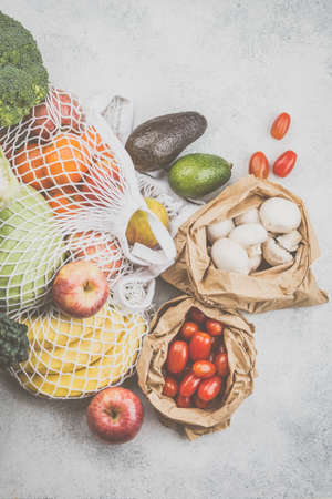 Zero waste eco friendly shopping concept, vegetables fruits in white mesh cotton and paper bags on white kitchen table, top view, toned, selective focus Stock Photo