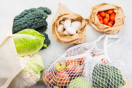 Zero waste eco friendly shopping concept, vegetables fruits in white mesh cotton and paper bags on white kitchen table, top view, selective focus Stock Photo
