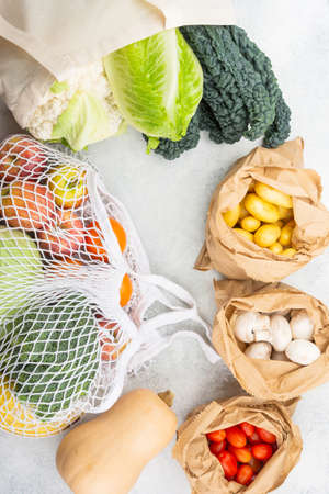 Zero waste eco friendly shopping concept, vegetables fruits in white mesh cotton and paper bags on white kitchen table, top view, selective focus Reklamní fotografie