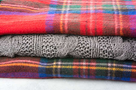 Stack of cosy winter wool blankets in tartan red, blue, grey colors, selective focus