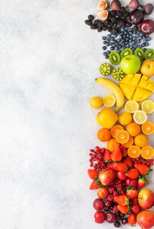 Rainbow fruits berries background on white. Top view of strawberries blueberries cherries mango apple lemons oranges red currants plums blackberries, selective focus