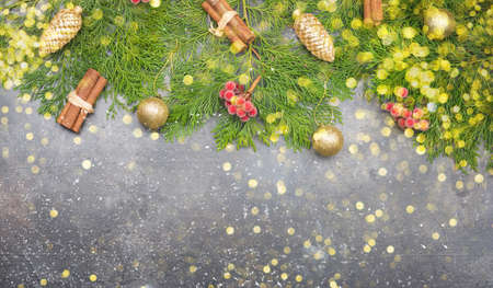 Festive Christmas background with fir tree branches, golden baubles and decorations with beautiful bokeh on grey concrete table, top view, copy space, selecitve focus