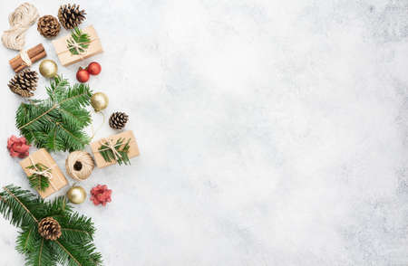 Christmas background. Top view of fir tree branches, brown gift boxes, various packing accessories, pinecones, tags on off white concrete table, copy space for text, selective focus