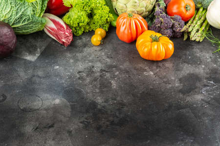 Fresh vegetables on dark grey and black background, top view, copy space, selective focus