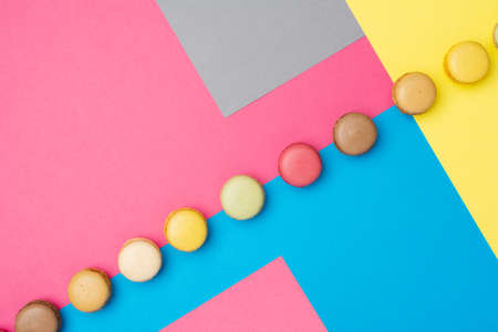 Classical french dessert. Colorful macarons arranged on creative pink grey blue yellow background, selective focus Foto de archivo - 135409191