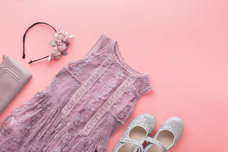 Toned photo of girls fashion background in pastel colors, lace and tulle dresses, flower headbands, flat lay, top view, selective focus
