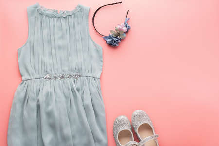 Girls fashion background blue tulle dress, sparkly shoes, flower headband on pink, flat lay, top view, toned photo, copy space for text, selective focus