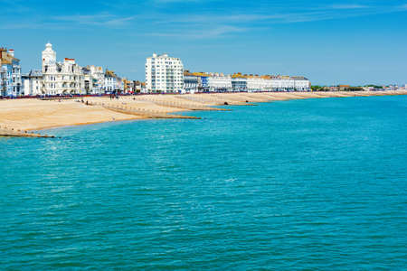 EASTBOURNE, EAST SUSSEX, UK - MAY 23 : View of Eastbourne town seafront, houses and beach from the pier in East Sussex on May 23, 2019
