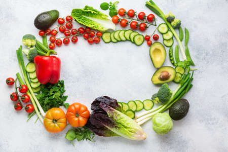 Fresh raw ingredients tomatoes cucumbers lettuce pepper avocado parsley spring onion broccoli peas arranged in a circle on the white table, top view, copy space, selective focus