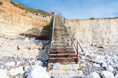 Staircase leading to Hope Gap beach in a low tide, near Seaford and Eastbourne, East Sussex, England, view of the chalk cliffs and stones, beach, selective focus