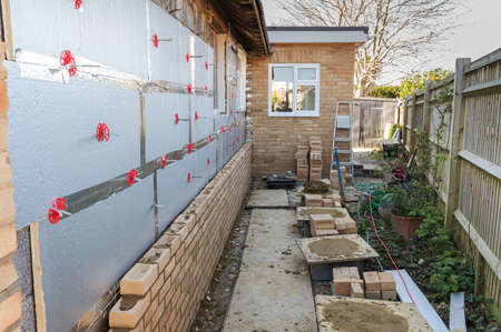 Bricklaying in residential property, renovation project, rows of bricks over insulation and block work, selective focus Stock Photo