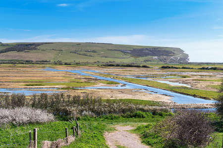 Walk to Cuckmere Haven beach near Seaford, East Sussex, England. South Downs National park. View of blue waters of the river, birds, selective focus