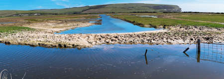 Walk to Cuckmere Haven beach near Seaford, East Sussex, England. South Downs National park. View of blue waters of the river, birds, panorama, long photo banner, selective focus