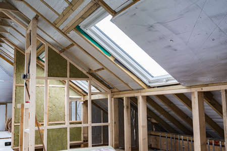 Loft conversion, unfinished project, silver insulation, roof windows, wood structure of the walls, selective focus
