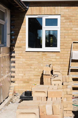 Preparation of the insulated wall for bricklaying in residential property, renovation project, rows of bricks, selective focus
