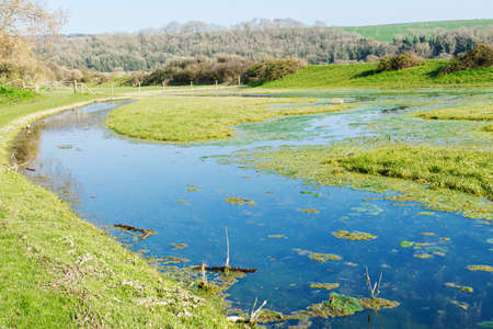 Walk in the countryside along Cuckmere river near Seaford, East Sussex, England. South Downs National park. View of blue waters of the river selective focus