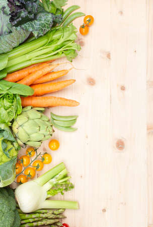 Top view of vegetables on wooden table, carrots celery tomatoes cabbage broccoli, copy space, selective focus