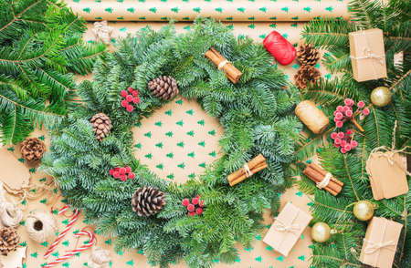 Top view of Christmas wreath on wrapping paper background, various accessories including fir tree branhes, pinecones and presents, selective focus