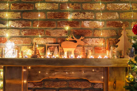 Beautiful decorated fireplace, wooden mantelpiece with fairy lights, handmade ornaments, candles and lantern, Christmas tree to the side, selective focus Stock Photo