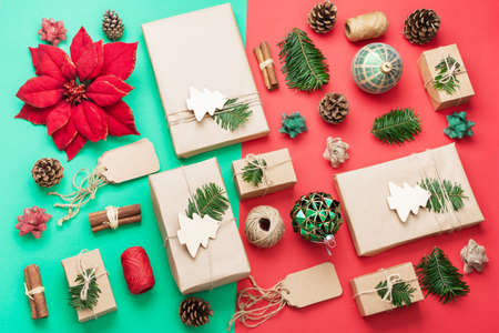 Zero waste Christmas composition in red green brown. Top view of presents wrapped in brown craft paper, pinecones, cinnamon sticks, jute twine and woden ornaments, baubles, selective focus Stock Photo