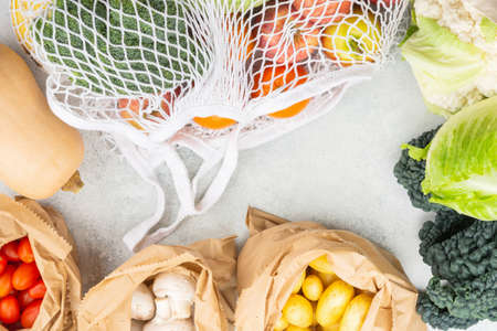 Eco friendly plastic free shopping concept, vegetables fruits in white mesh cotton and paper bags on white kitchen table, top view, selective focus