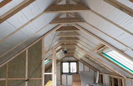 Loft conversion, unfinished project, silver insulation, roof windows, wood structure of the walls, selective focus Stock Photo