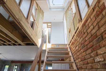 Stairs leading to the loft conversion, unfinished project, plastered walls, roof windows, wood structure of the walls, selective focus Banque d'images