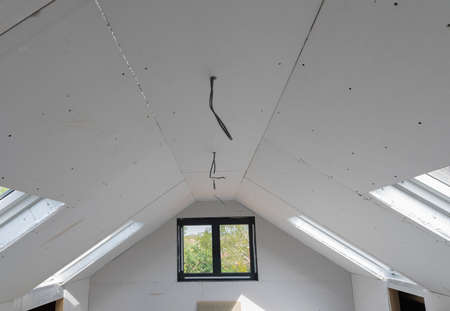 Loft conversion, unfinished project, plaster boarded walls and ceiling, roof windows wood structure, selective focus