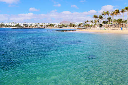 Beautiful beach of Las Cucharas in Costa Teguise, Lanzarote, Canary Islands. View of the blue sea, yellow sand, palm trees, selective focus
