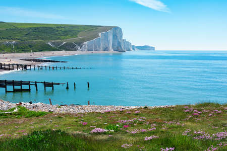 Walking route in Cuckmere beach near Seaford, East Sussex, England. South Downs National park. View of blue sea, cliffs, beach, green fields, selective focus