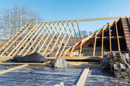 Unfinished wooden structure of house roof, extension of the roof space, beams and trusses, partially tiled, selective focus Zdjęcie Seryjne