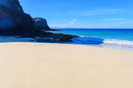 View of beautiful Playa de la Cera beach, blue sea, yellow sand, cliffs. Papagayo, Playa Blanca, Lanzarote, Canary Islands. VIew of Fuerteventura on the background, selective focus 版權商用圖片