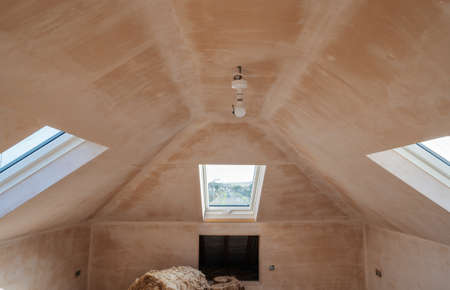 Brown plastered walls in the property, preparation for the paint. Loft conversion with rounded ceilings, roof windows selective focus Stock fotó