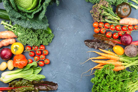 Colourful vegetables background, copy space for text, Broccoli cauliflower carrots tomatoes kale pak choy onions parsley. Healthy local farm produce on blue concrete table, top view, selective focus Stok Fotoğraf