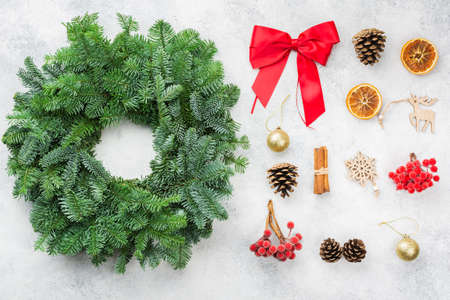 Handmade Christmas wreath on the white table, with accessories for decoration inclucing red berries, pine cones bow, cinnamon sticks golden baubles, top view, selective focus