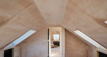 Brown plastered walls in the property, preparation for the paint. Loft conversion with rounded ceilings, roof windows selective focus
