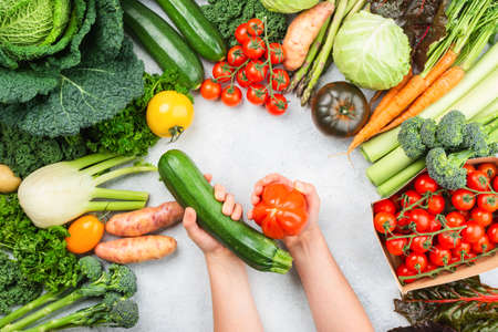 Healthy eating concept, Hands holding vegetables. Organic vegetables broccoli cauliflower carrots kale pak choy onions. Healthy local farm produce on white wooden table, top view, selective focus