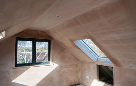 Brown plastered walls in the property, preparation for the paint. Loft conversion with straight corners ceilings, roof windows selective focus Archivio Fotografico