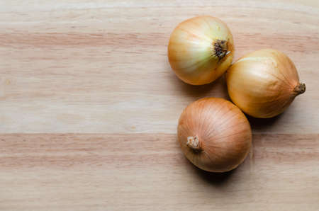 Three large white onions that have not been peeled off, are placed on the background of softwood materials that are smooth and beautiful.