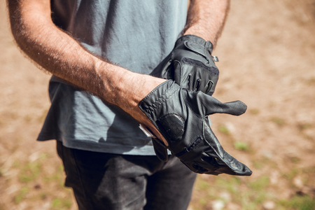 Man putting on gloves for riding in the forest of Andorra Banco de Imagens